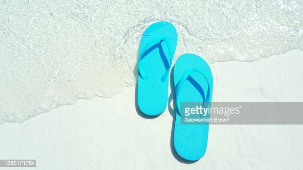 travel background with a pair of yellow flip-flops in the sand of a beautiful beach, maldives - スリッパ ストックフォトと画像