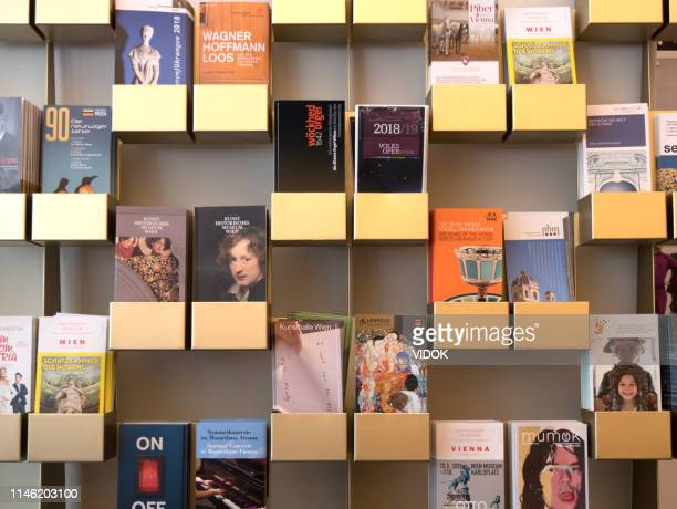 travel brochures and maps on shelves in vienna, austria. - brochure stock pictures, royalty-free photos & images