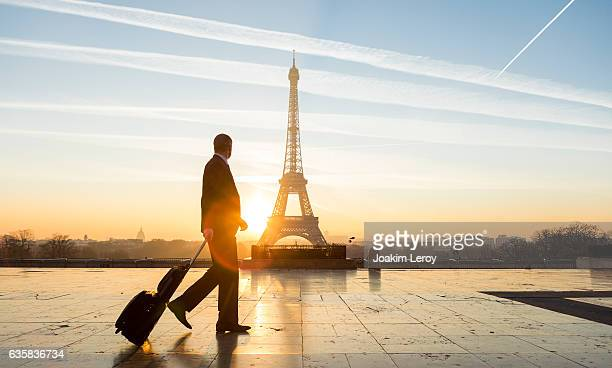 travel businessman walking with suitcase at eiffel tower in paris - geschäftsreise stock-fotos und bilder