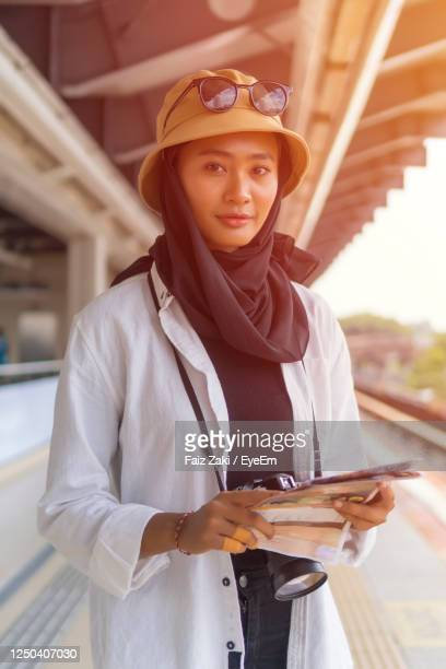 travel concept, muslim tourist woman at kuala lumpur studying a map at the train station - zurückhaltende kleidung stock-fotos und bilder
