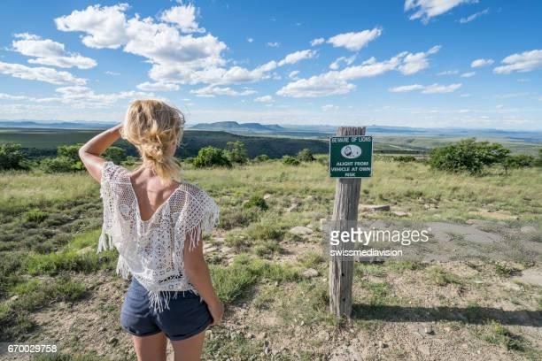 Travel girl contemplating landscape, lion warning sign