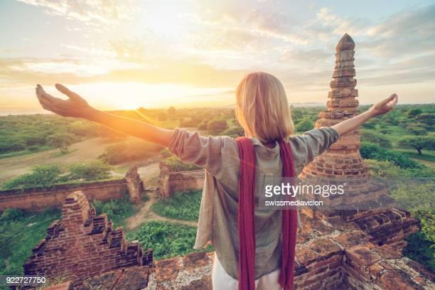 Travel girl embracing Bagan temples at sunrise, Myanmar