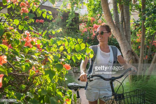 Travel girl pushing bicycle in tourist resort in the morning