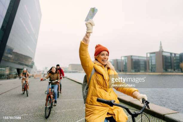 travel guide and her group on the bicycles through the town - middelgrote groep mensen stockfoto's en -beelden