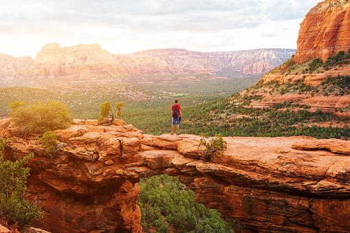 Travel in Devil's Bridge Trail, man Hiker with backpack enjoying view, Sedona, Arizona, USA 885620720