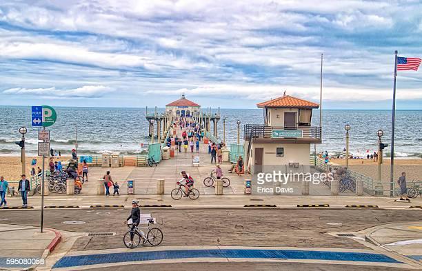 Travel Like a Local - Brief- Bike riders ride and beach goers walk along Huntington Beach.