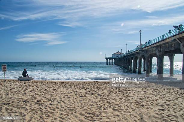 travel like a local - brief- young surfer sits on his surf board at huntington beach. - huntington beach stock pictures, royalty-free photos & images