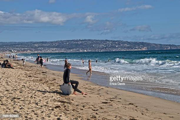 travel like a local - brief- young surfer sits on his surf board while others relax and swim at huntington beach. - category:cs1_maint:_others stock pictures, royalty-free photos & images