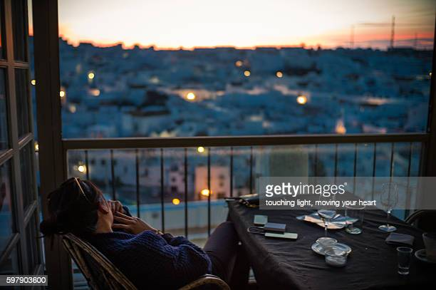 travel like a local - yong female tourist drinking and enjoying stunning sunset view in spanish white town - vejer de la frontera fotografías e imágenes de stock