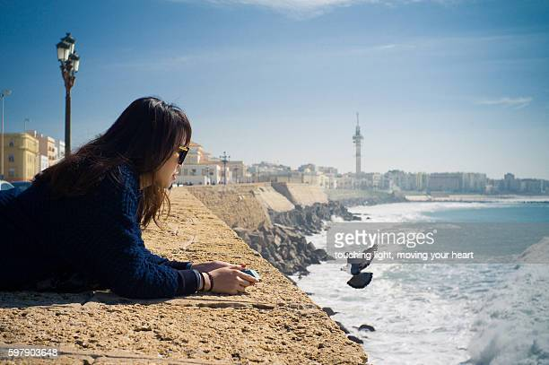 Travel like a local - young female tourist looking at sea of Cadiz