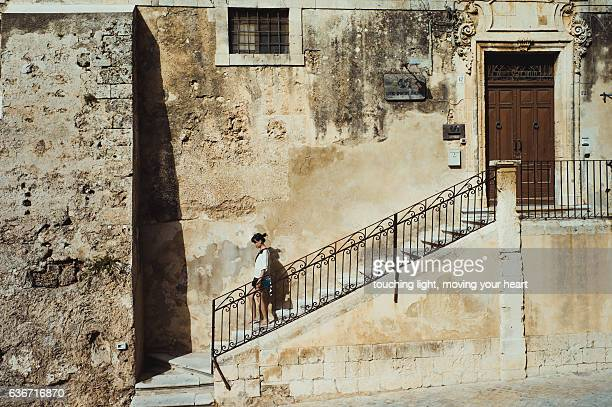 Travel Like a Local - Young female tourist walking down steps in front of an old building in UNESCO city Noto, Sicily, Italy