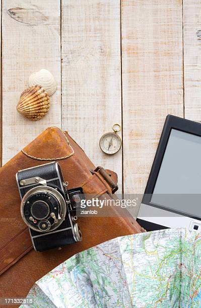 Travel objects. Suitcase, camera, map, compass, ebook and shells.