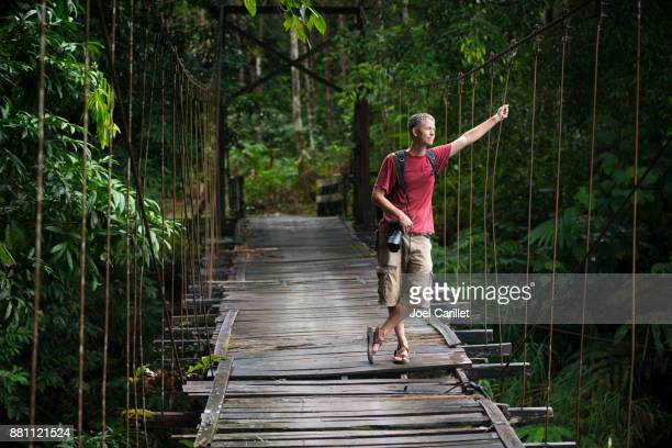Travel photographer hiking with DSLR camera in Kalimantan, Indonesia