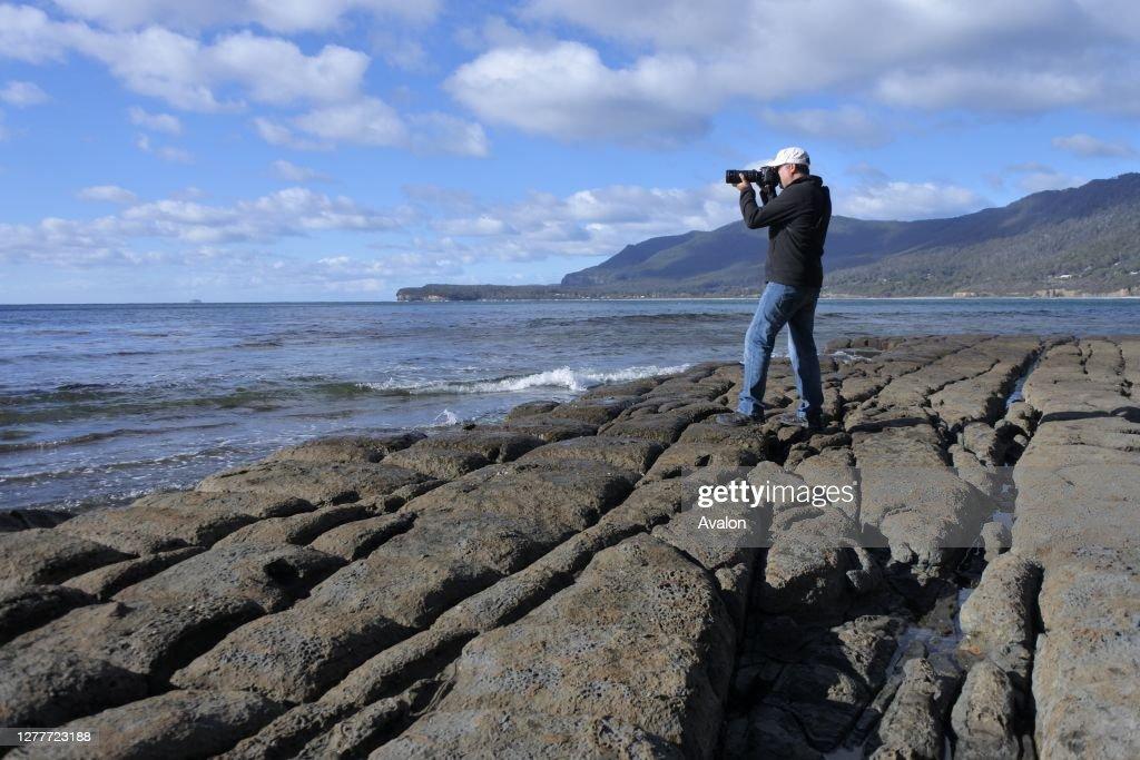Travel photographer photographing Tessellated Pavement in Tasman Peninsula Tasmania Australia. : News Photo