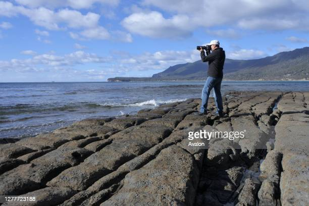 Travel photographer photographing Tessellated Pavement in Tasman Peninsula Tasmania Australia.