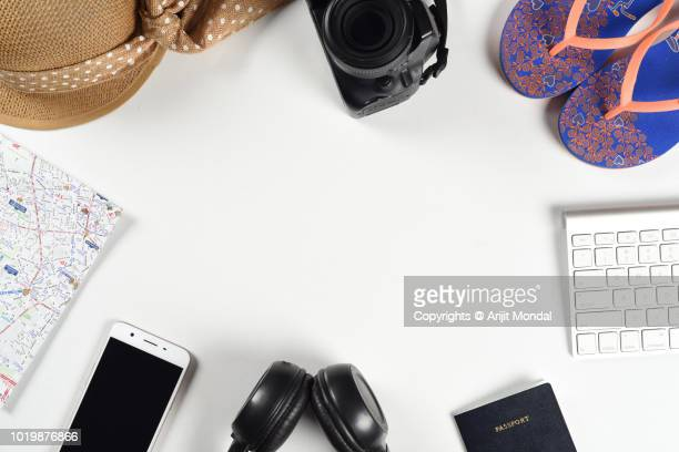 travel preparations concept with digital slr camera, footwear, computer keyboard lot of things on white wooden table - accessoires stock-fotos und bilder