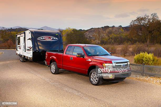 travel star trailer pulled by f150 ford pickup at sunset - towing stock photos and pictures