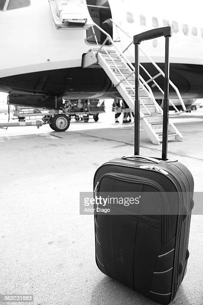 Travel: suitcase in front of airplane