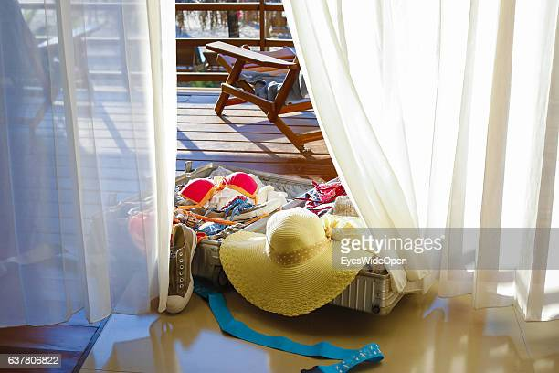 Travel suitcase with shoes bikini and clothes a tourist woman with a sun hat work with notebook and handy in a lounger on a balcony at the white...