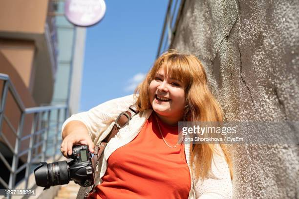 travel, tourism and entertainment. plus size woman photographer working at the street - fat blonde women stock pictures, royalty-free photos & images