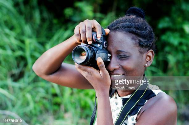 travel, tourism and hobby. young woman photographer taking pictures in the bush. - côte d'ivoire stock pictures, royalty-free photos & images