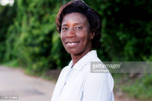 travel, tourism, smiling young woman in the field - côte d'ivoire stock pictures, royalty-free photos & images
