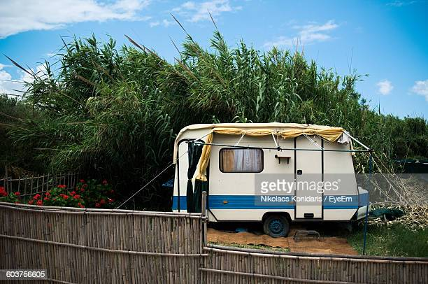 Travel Trailer Parked Against Trees On Field