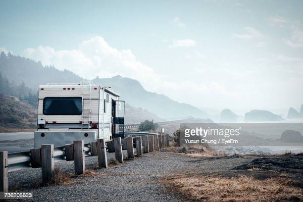travel trailer parked on roadside by mountain against sky - camper trailer stock pictures, royalty-free photos & images