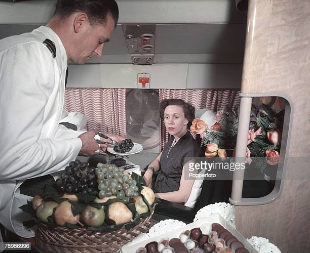 Travel Transport Aviation pic A steward on board a BOAC Britannia serving fresh fruit and chocolate sweets for a passenger