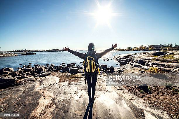 travel woman arms outstretched by the sea - helsinki stockfoto's en -beelden