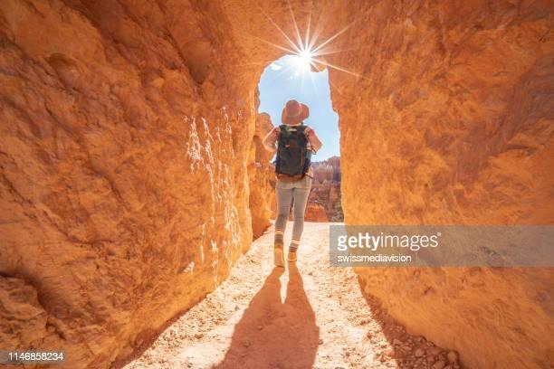 a mulher do curso explora a garganta com trouxa em ombros; conceito dos destinos de viagem da descoberta dos povos. menina que anda através do túnel na garganta de bryce - bryce canyon - fotografias e filmes do acervo
