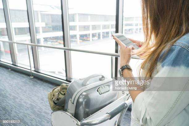 Travel woman playing mobile phone with Trolley luggage in the airport