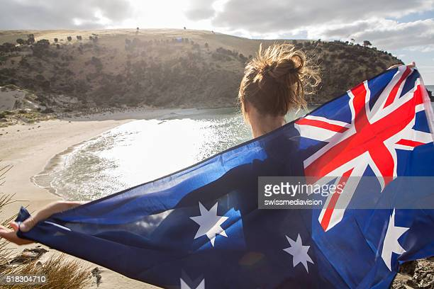 Travel woman stands on cliff above beach holding Australian's flag