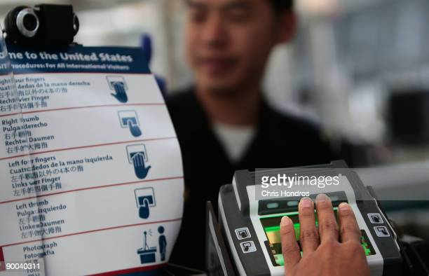 A traveler arriving from overseas is fingerprinted while his paperwork is checked by a border patrol official at the passport control line in Newark...