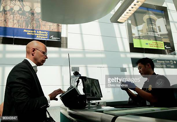 A traveler arriving from overseas is fingerprinted while his paperwork is checked in a passport control line upon arriving to Newark International...