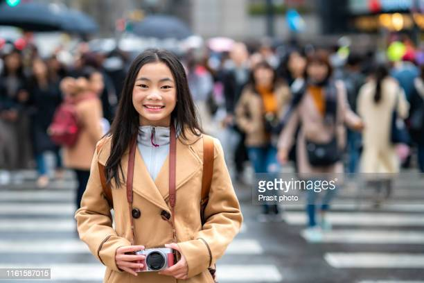 traveler asian woman with camera standing and smiling at the crosswalk in the city of seoul. south korea. - korean culture stock pictures, royalty-free photos & images