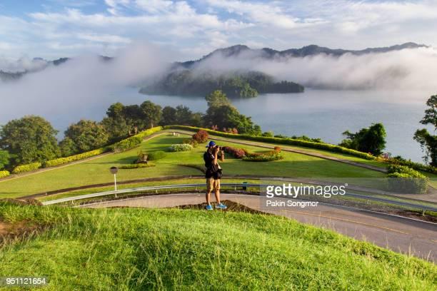 traveler asian young man take a photo at rajjaprabha dam, surat thani province - kao sok national park stock pictures, royalty-free photos & images