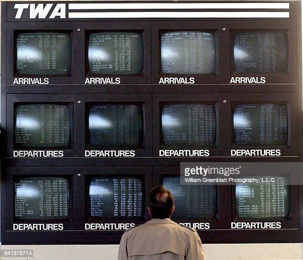 A traveler at LambertSt Louis International Airport checks flight information at a bank of Trans World Airlines monitors in the main terminal...