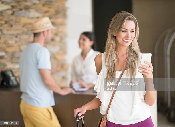 Traveler at the hotel using app on her cell phone