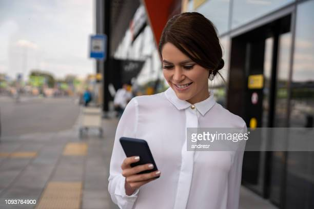 traveler calling a taxi outside the airport using her cell phone - auto repair shop exterior stock pictures, royalty-free photos & images