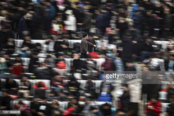 A traveler carries his luggage through the main hall of the Shanghai Hongqiao Railway Station in Shanghai China on Wednesday Jan 30 2019 Chinese New...