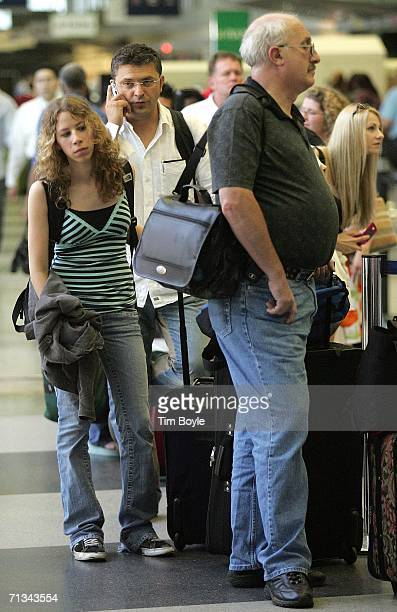 Traveler chats on his cell phone while waiting in line in Terminal 3 June 30, 2006 at O'Hare International Airport in Chicago, Illinois. Heavy...