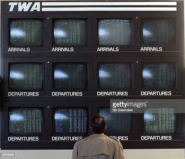 A traveler checks flight information at a bank of Trans world Airlines monitors in the main terminal January 9 2001 at LambertSt Louis International...