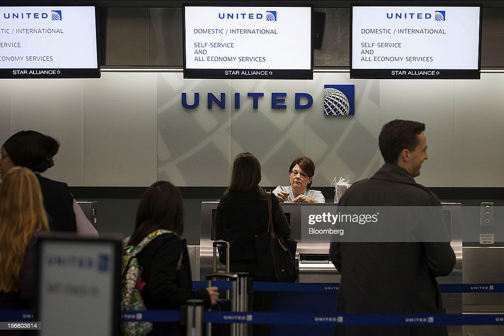 A traveler checks in with United Continental Holdings ticket agent at LaGuardia Airport in the Queens borough of New York, U.S., on Wednesday, Nov. 21, 2012. U.S. travel during the Thanksgiving holiday weekend will rise a fourth straight year, gaining 0.7 percent from 2011, as trips by automobile rise even as airplane trips decline, AAA said last week. Photographer: Michael Nagle/Bloomberg via Getty Images