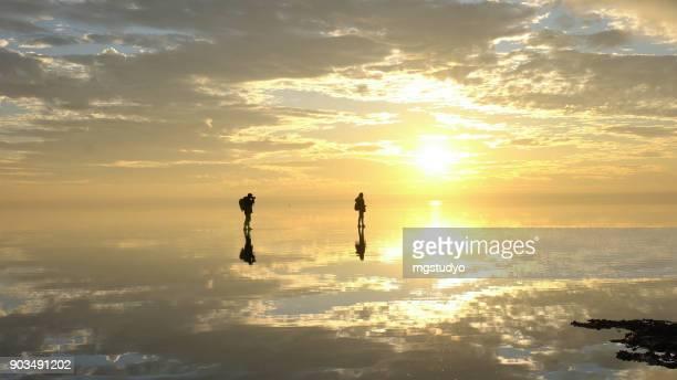 Traveler couple having fun walking on salt lake at sunset