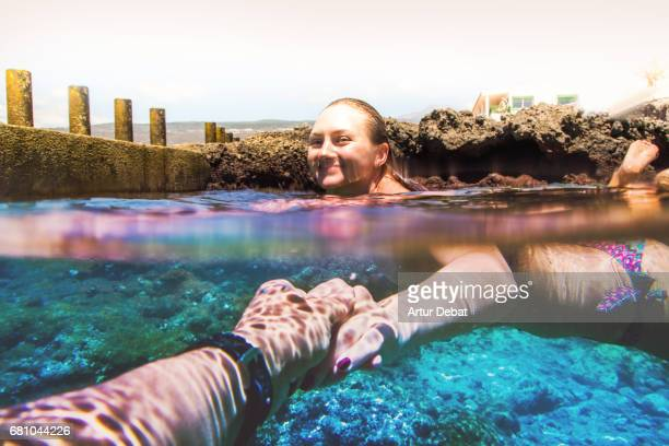Traveler couple in love swimming and enjoying alone the natural pool during travel vacations in the Tenerife island with nice water colors, relaxing moment in stunning place, and picture taken from personal perspective of the boyfriend.