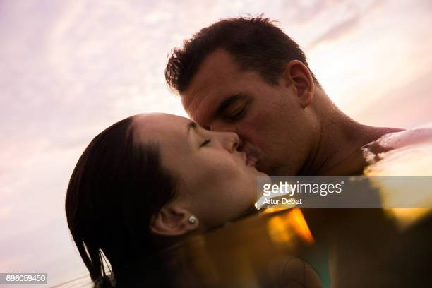 Traveler couple swimming on water kissing during the sunset moment taking a selfie after long day during travel vacations in the paradise islands of Indonesia with stunning colors in the sky and reflections on water.