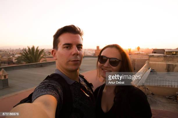 Traveler couple taking a selfie with the Marrakech cityscape during sunset taken from building terrace with mosque silhouettes and nice colors in the sky during travel vacations in Morocco.