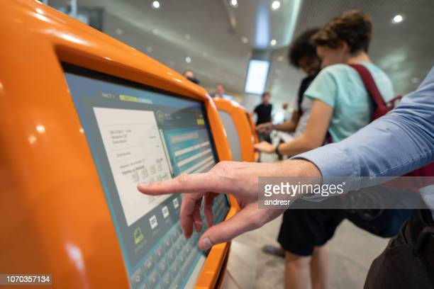 traveler doing a self check-in at the airport - kiosk stock pictures, royalty-free photos & images