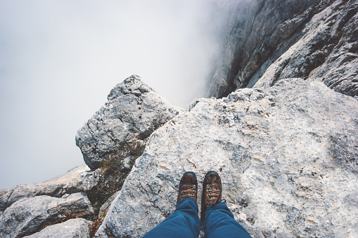 Traveler Feet boots on rocky mountain cliff over foggy clouds Travel Lifestyle success concept adventure active vacations outdoor top view 1032757482